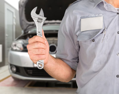 automotive mechanic holding wrenches